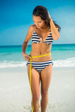 Pretty brunette measuring waist at the beach Royalty Free Stock Photo