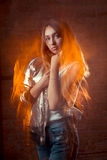 Pretty brunette model in shiny silver jacket and blue jeans. Mix Stock Image