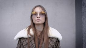 Pretty brunette model is standing outdoors in autumn day, she is wearing warm trendy coat with fur collar and sunglasses stock video footage
