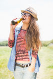 Pretty brunette in the park drinking beer Royalty Free Stock Photography