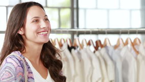 Pretty brunette paying with card at clothing store stock footage