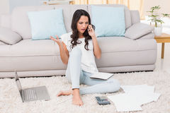 Pretty brunette paying her bills Stock Image