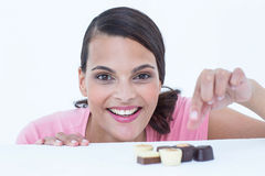 Pretty brunette peeking at chocolate looking at camera Royalty Free Stock Photos