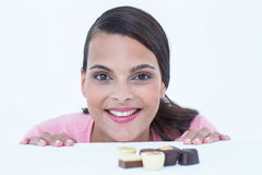 Pretty brunette peeking at chocolate looking at camera Royalty Free Stock Images
