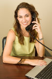 Pretty brunette on the phone. A pretty brunette business professional on the phone, wearing a green outfit Royalty Free Stock Photo