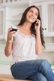 Pretty brunette on the phone having glass of wine Stock Photo