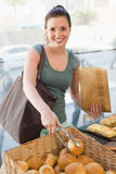 Pretty brunette picking out bread roll Stock Photos
