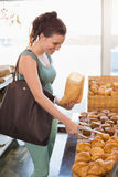 Pretty brunette picking out croissant Royalty Free Stock Images