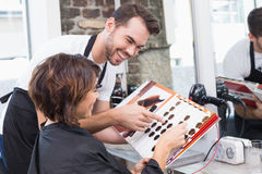 Pretty brunette picking out hair colour with stylist. At the hair salon stock photos