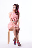 Pretty brunette in a pink dress sitting on a chair on a white ba Stock Photography