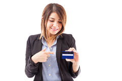 Pretty brunette pointing at a credit card Royalty Free Stock Image