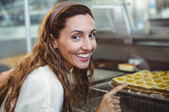 Pretty brunette pointing at pastries through the glass Royalty Free Stock Photos