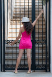 Pretty brunette posing in front of the iron gate Stock Photography