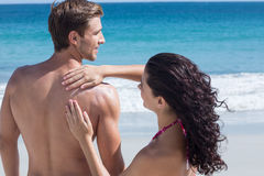 Pretty brunette putting sun tan lotion on her boyfriend Stock Photography