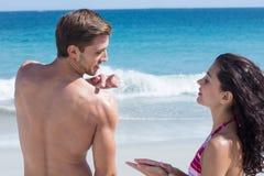 Pretty brunette putting sun tan lotion on her boyfriend Stock Photography