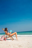 Pretty brunette reading a book on deck chair Royalty Free Stock Photo