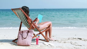 Pretty brunette reading a book on deck chair. At the beach stock video footage