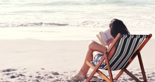 Pretty brunette reading a book on deck chair. At the beach stock video