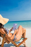 Pretty brunette reading on deck chair at the beach Royalty Free Stock Photos