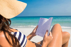 Pretty brunette reading on deck chair at the beach Royalty Free Stock Photography