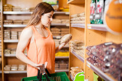 Pretty brunette reading a product label. Young woman carrying a basket and reading a product label at a grocery store Royalty Free Stock Photo