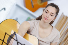 Pretty brunette reading sheet music and playing guitar. Pretty brunette reading a sheet music and playing the guitar Stock Images