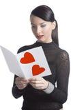 Pretty brunette reads valentine postcard Stock Photos