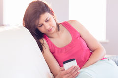 Pretty brunette relaxing on the couch using smartphone Stock Images