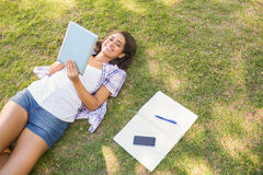 Pretty brunette relaxing in the grass and reading book Royalty Free Stock Photo