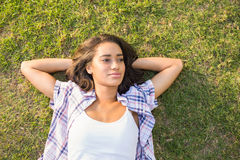 Pretty brunette relaxing in the grass Stock Image
