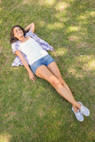 Pretty brunette relaxing in the grass Royalty Free Stock Photos