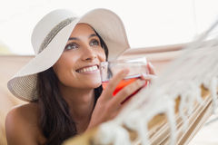 Pretty brunette relaxing on a hammock and drinking cocktail Royalty Free Stock Image