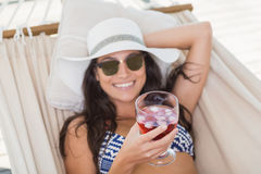 Pretty brunette relaxing on a hammock and drinking cocktail Royalty Free Stock Photography