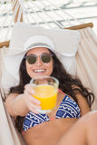 Pretty brunette relaxing on a hammock and drinking orange juice Stock Images