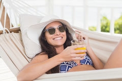 Pretty brunette relaxing on a hammock and drinking orange juice Royalty Free Stock Photography