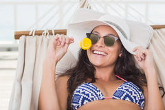 Pretty brunette relaxing on a hammock and eating a lollipop Royalty Free Stock Image