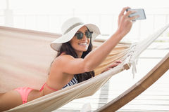 Pretty brunette relaxing on a hammock and taking selfie Royalty Free Stock Images