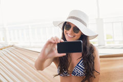 Pretty brunette relaxing on a hammock and taking selfie Royalty Free Stock Image