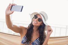 Pretty brunette relaxing on a hammock and taking selfie Royalty Free Stock Photography