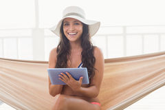 Pretty brunette relaxing on a hammock and using tablet pc Royalty Free Stock Photos