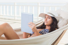 Pretty brunette relaxing on a hammock and using tablet pc Stock Images