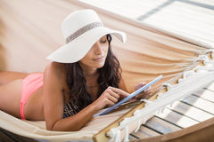 Pretty brunette relaxing on a hammock and using tablet pc Stock Photos