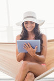 Pretty brunette relaxing on a hammock and using tablet pc Royalty Free Stock Photography