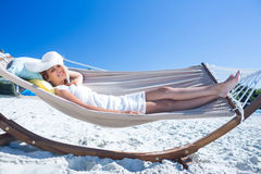 Pretty brunette relaxing with her straw hat in the hammock Royalty Free Stock Image