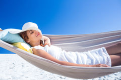 Pretty brunette relaxing with her straw hat in the hammock Stock Photos