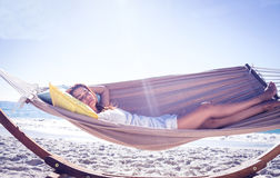 Pretty brunette relaxing with her straw hat in the hammock Stock Photography