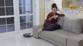 Pretty brunette relaxing at sofa while vacuum-cleaning robot clean the floor. Young woman sits at the sofa at home and relaxes with her phone. The vacuum stock video