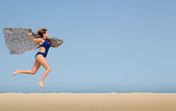 Pretty brunette running in the sand Royalty Free Stock Photography