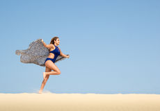 Pretty brunette running in the sand Stock Photo