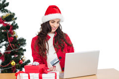 Pretty brunette in santa hat shopping online with laptop Royalty Free Stock Photos